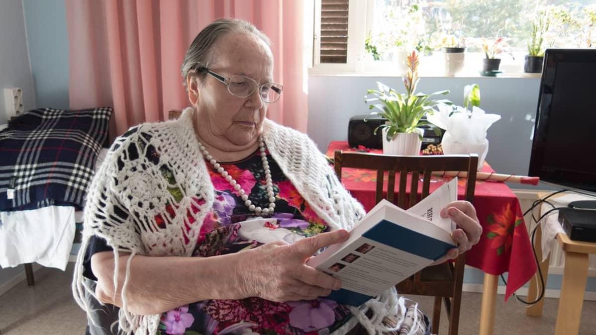 Terttu Mikkola lukee kirjaa huoneessaan.