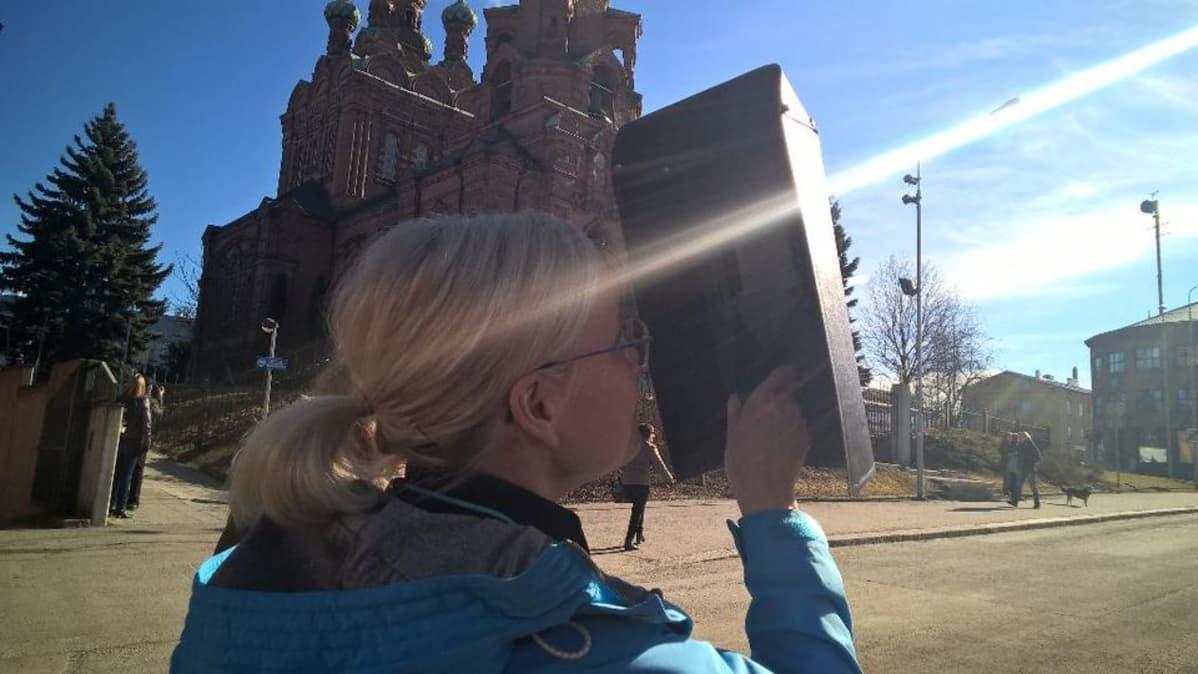 Nainen katsoo auringonpimennystä hitsauslaisen läpi Tampereella