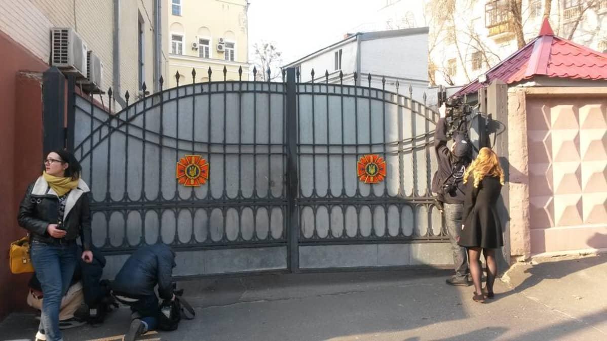 Kuvaajat yrittävät saada kuvia hätätilaviraston takapihalta.