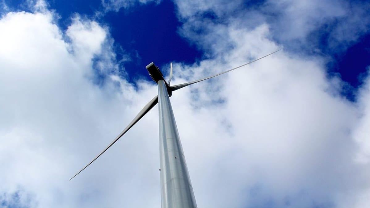Tuulivoimala puolipilvistä taivasta vasten.