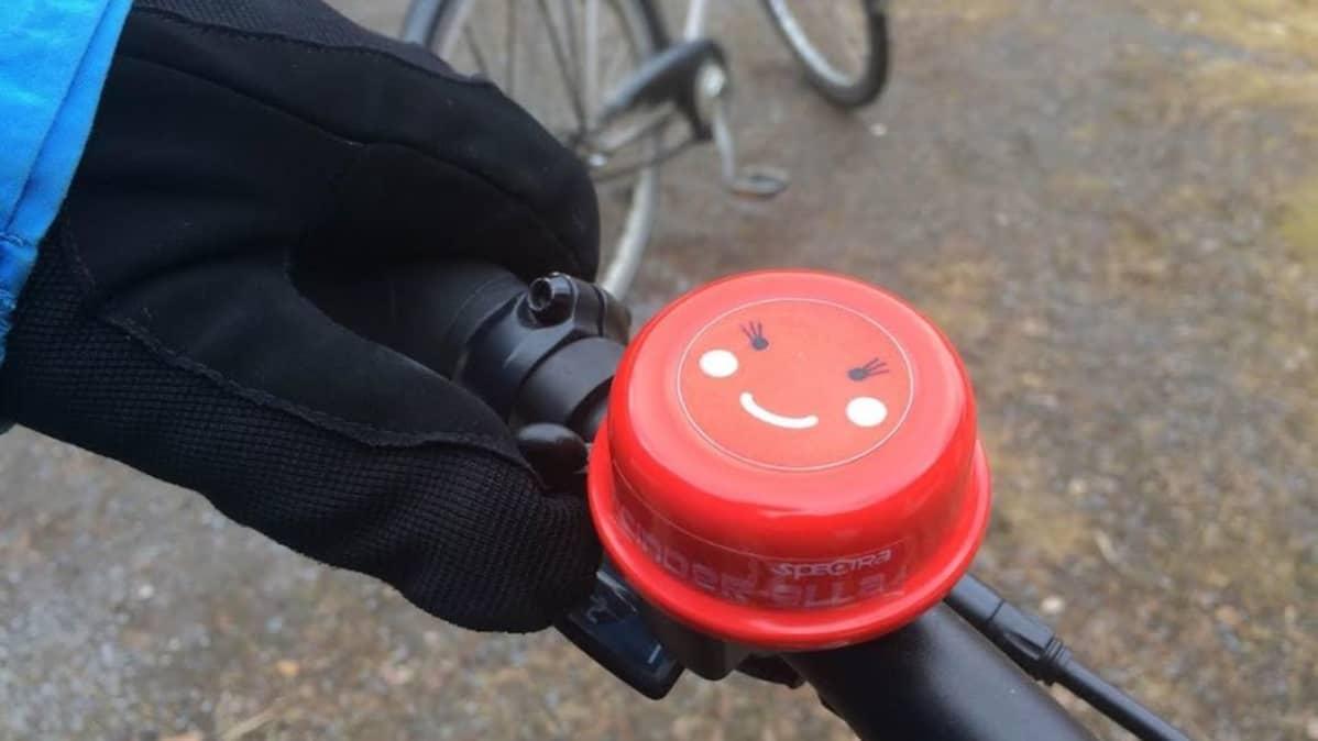 Polkupyörän punainen soittokello, jossa hymynaama.