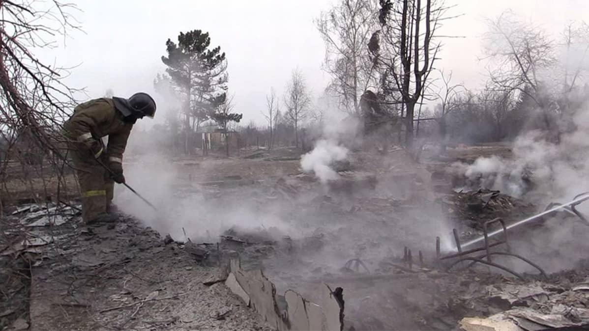 Palomies sammuttaa savuavaa rauniota.