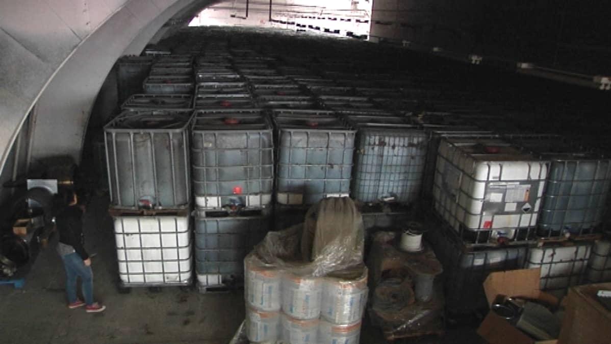 Teräsvahvisteisia jätekontteja pakattuina tiukkaan hallissa