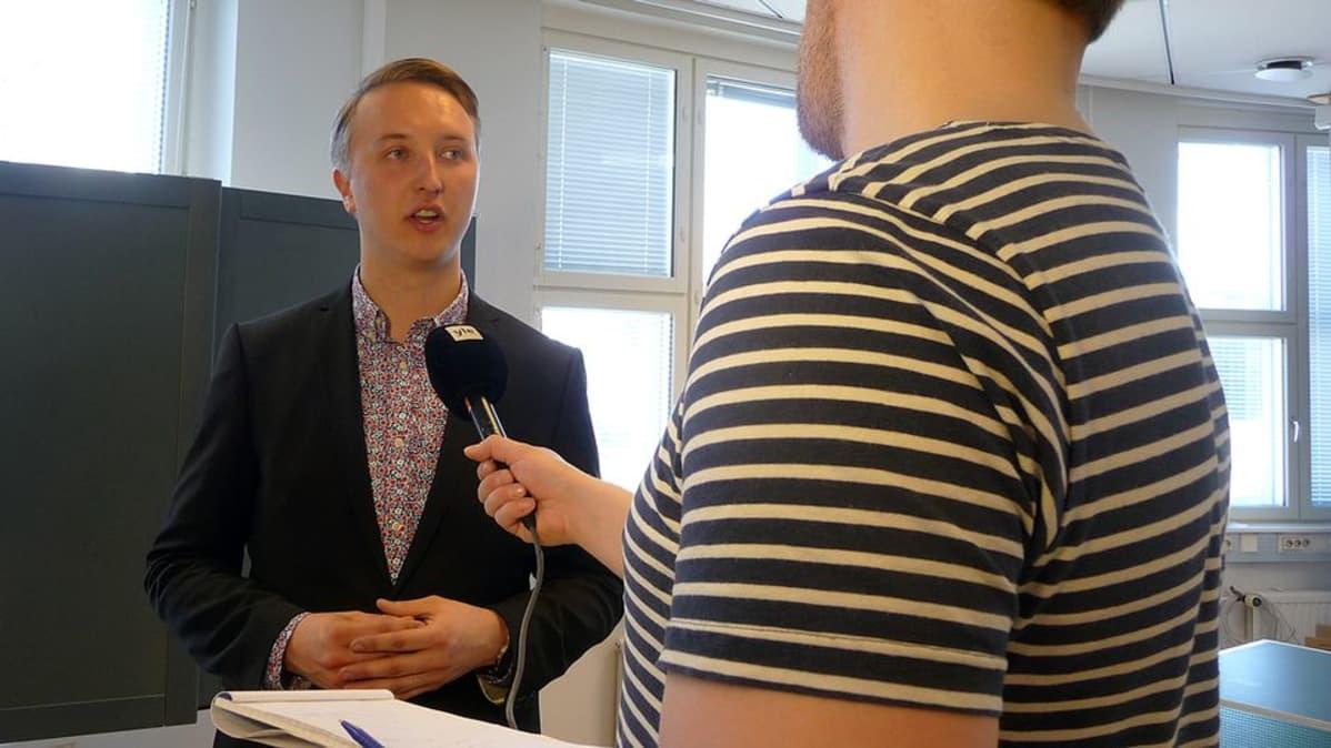 Toimittaja haastattelee Ilmari Nurmista