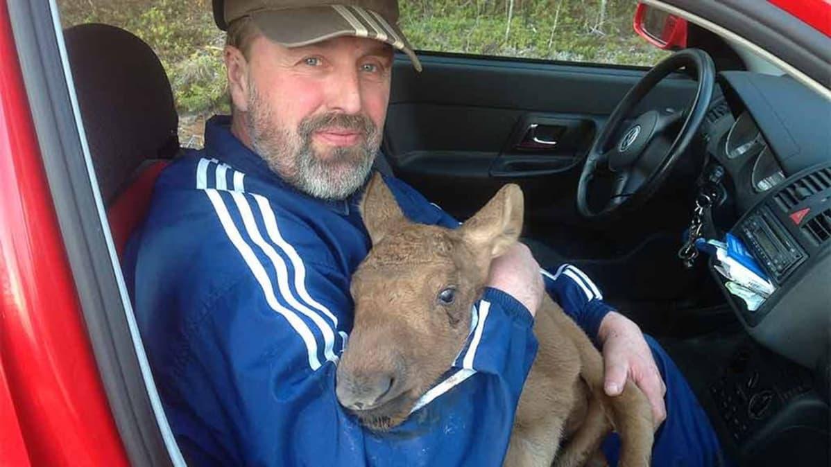 Kuvassa Mikko Perander istuu autossa vasa sylissä.