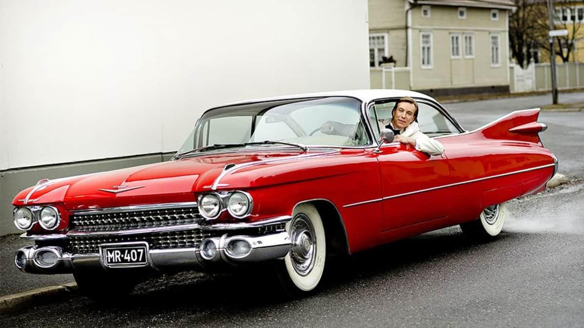 """Kuvassa punainen """"amerikanrauta"""", jossa istuu kuljettaja."""