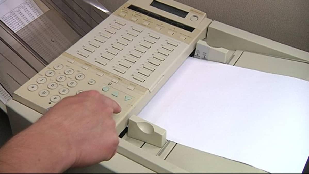 Mies näppäilee faksin numeroita.