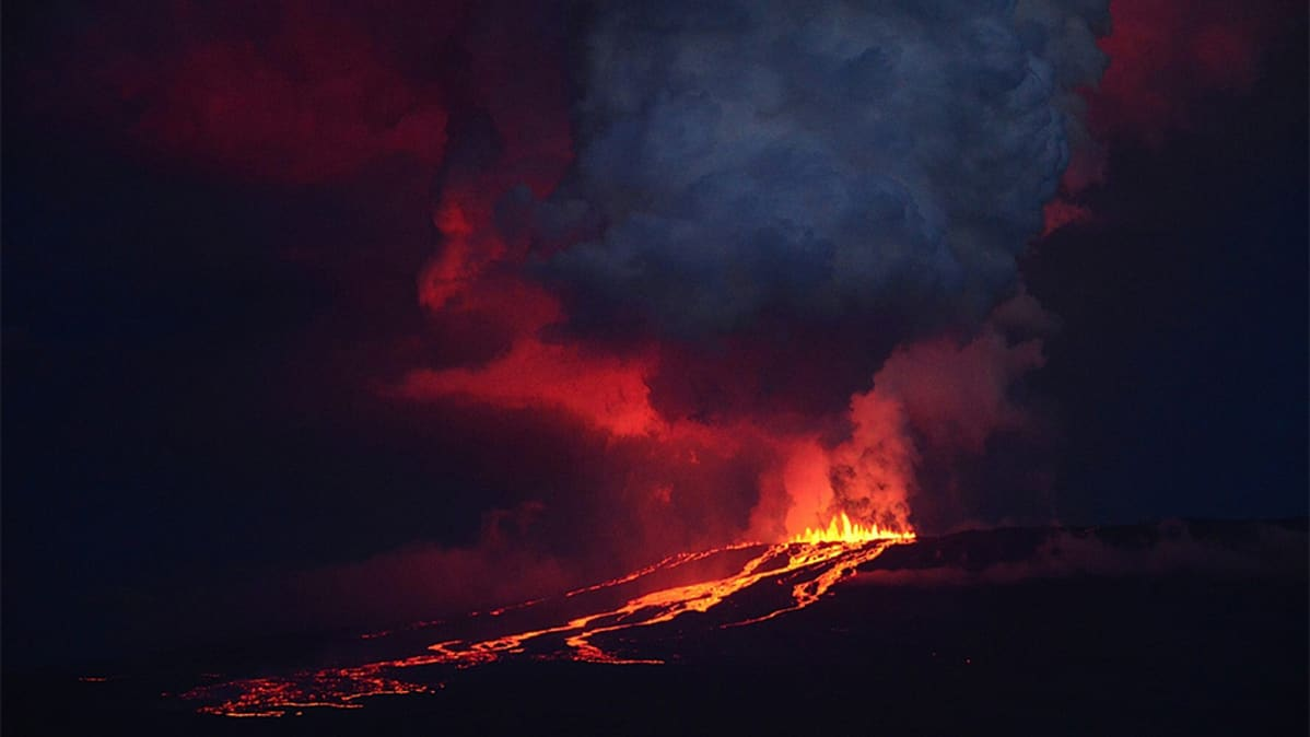 Purkautuva tulivuori yökuvassa.