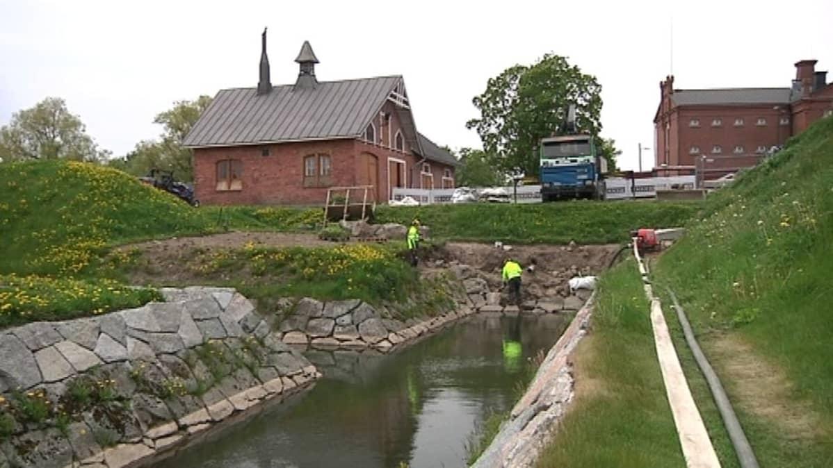 Miehiä työssä vedellä täyttyneellä vallihaudalla
