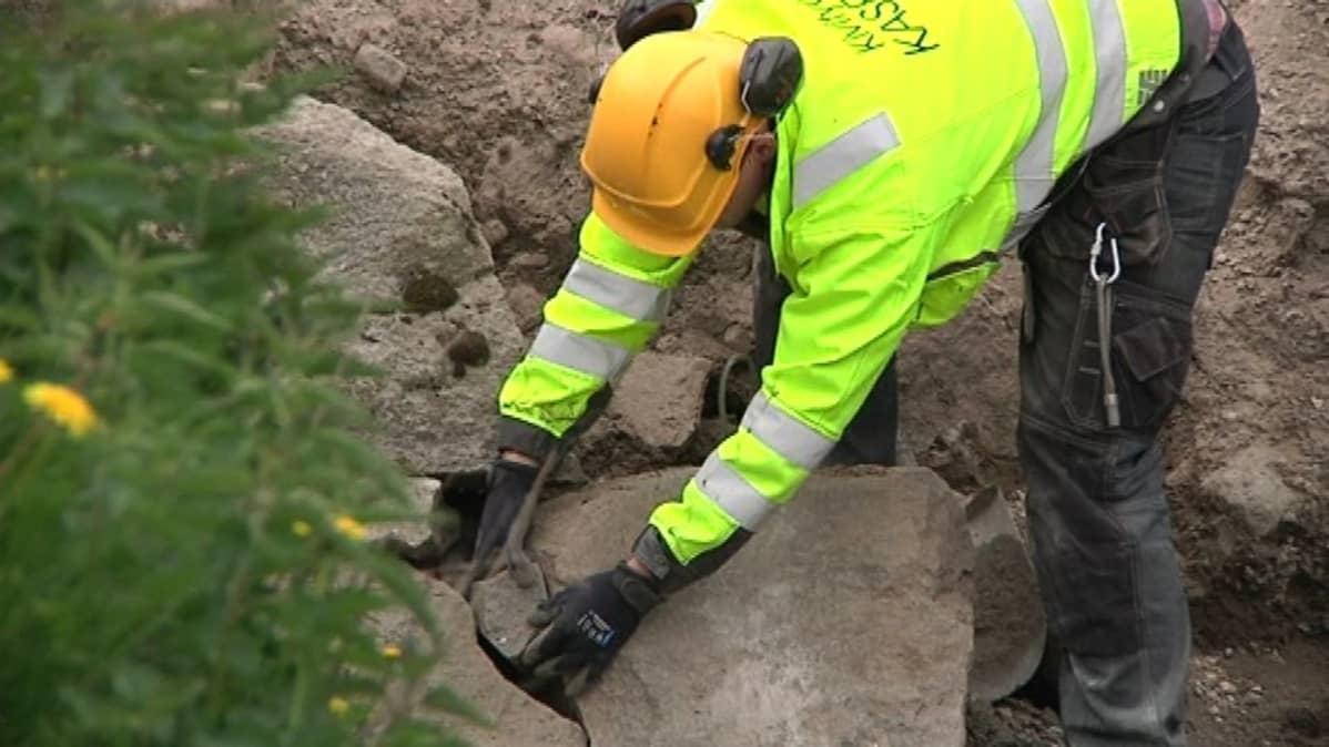Mies asettelee kiviä vallihaudan muuriin paikalleen