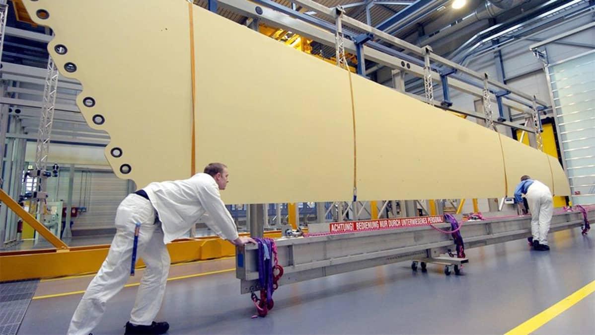 Työntekijä siirtävät siiven osaa tehtaalla.