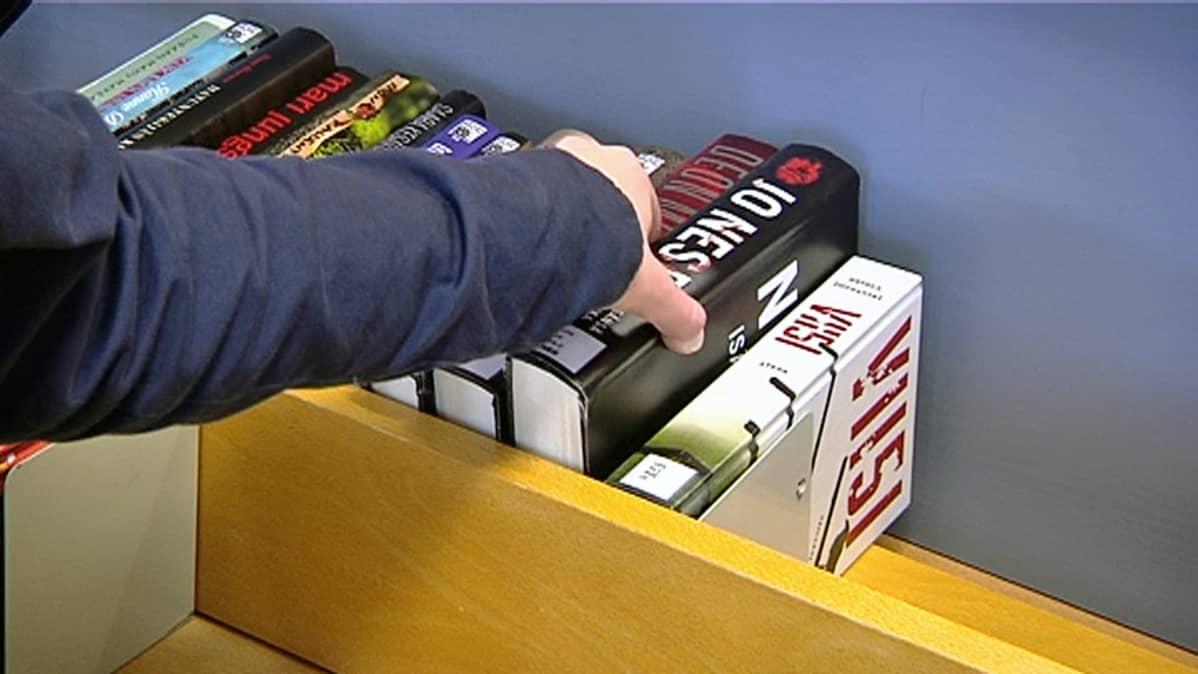 Henkilö ottamassa käteensä Jo Nesbon kirjaa kirjastossa.