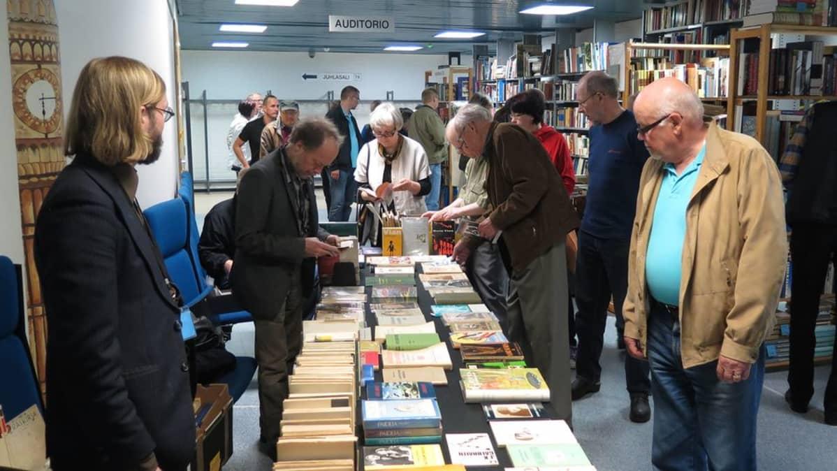 Ihmiset tutkivat myyntipöydän kirjoja.