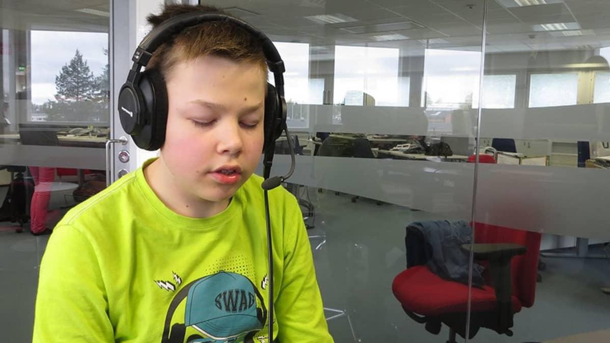 Ville Köngäs istuu studiossa luurit päässä.