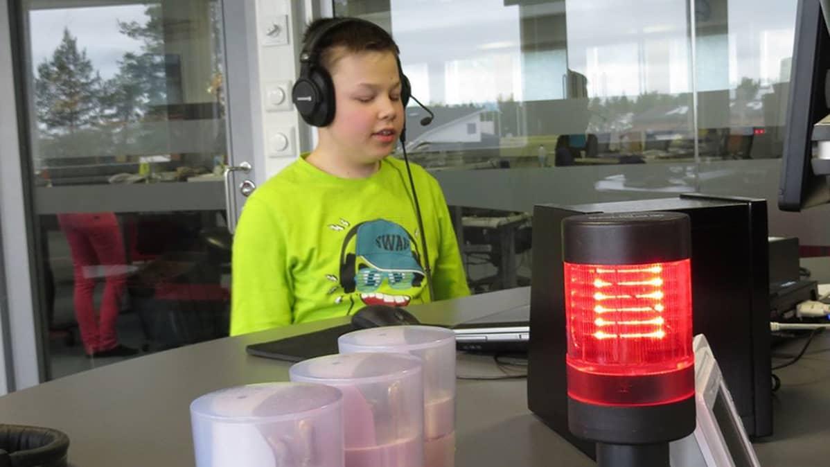 Ville Köngäs istuu studiossa ja punainen lähetysvalo palaa.