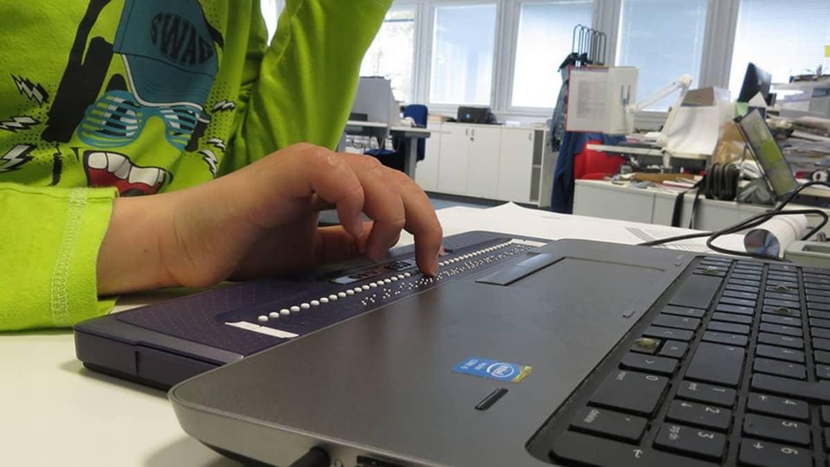 Ville Köngäs kirjoittaa läppärillä, jossa on sokeille oma lisälaite braille-pistekirjoitukselle.