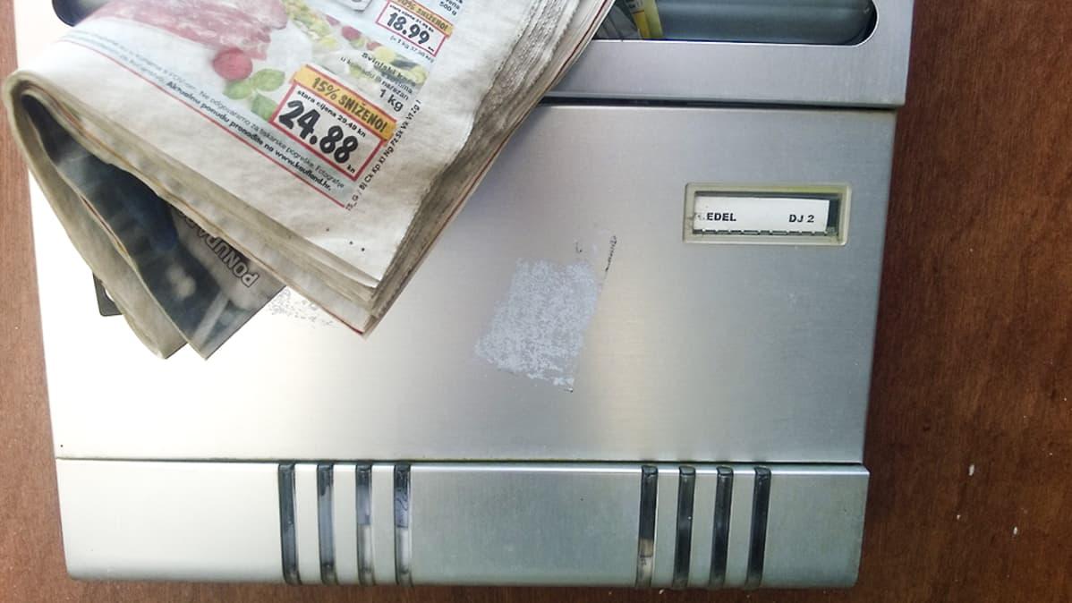 """Konstantin Edelin talon postilaatikko. Postilaatikossa on hieman ryppyiseltä näyttävä sanomalehti ja nimikyltti, jossa lukee: """"EDEL   DJ 2""""."""