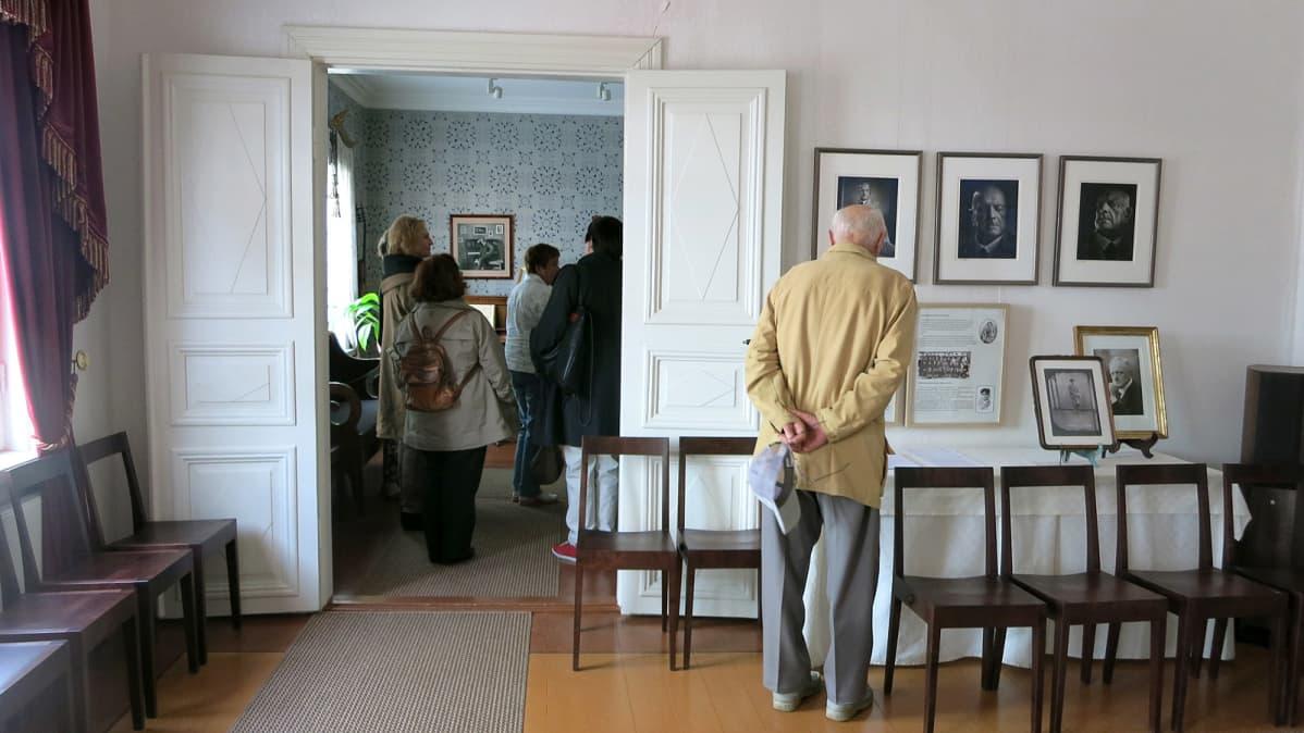 Sibeliuksen syntymäkodissa mies katsoo Sibelius-valokuvaa