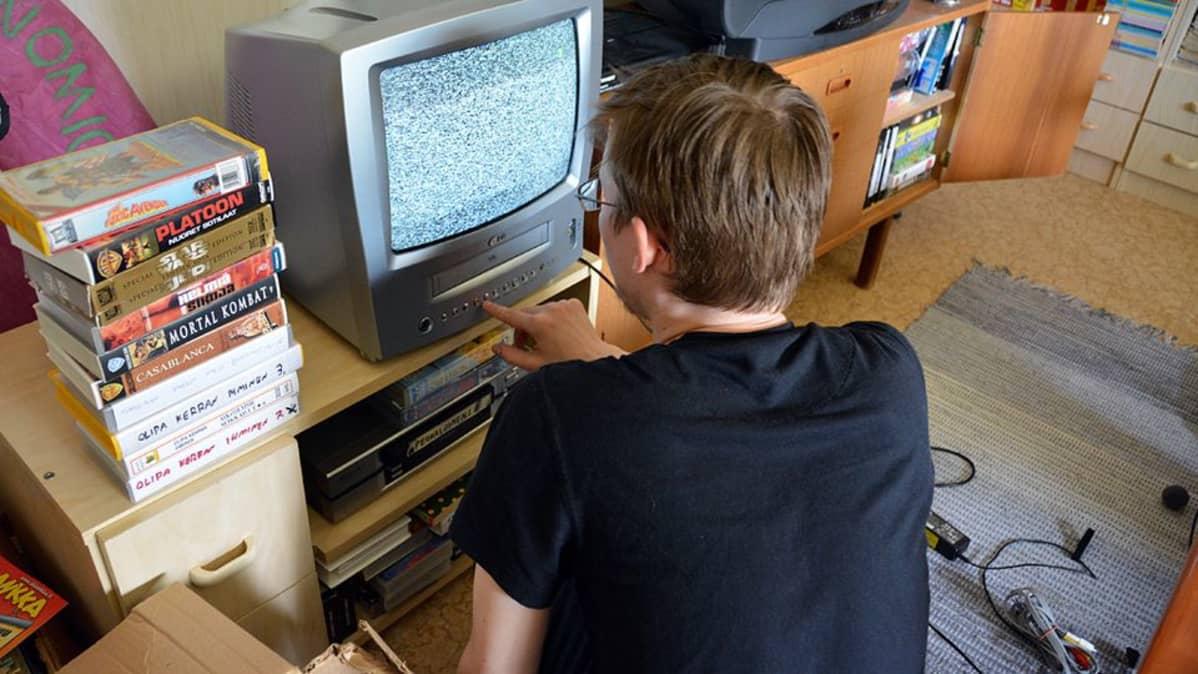 Mies virittää televisiotaan.