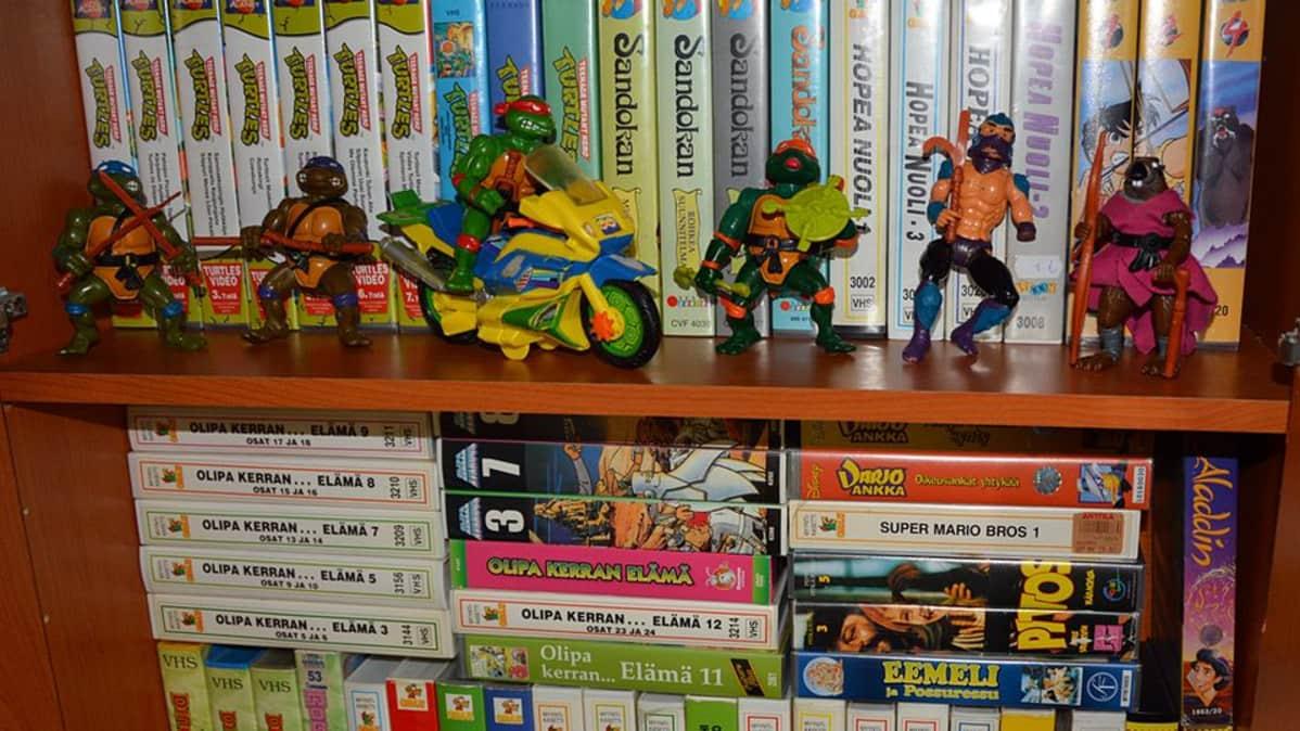 Hyllyssä Turtles-lelufiguureja sekä vhs-kasetteja.