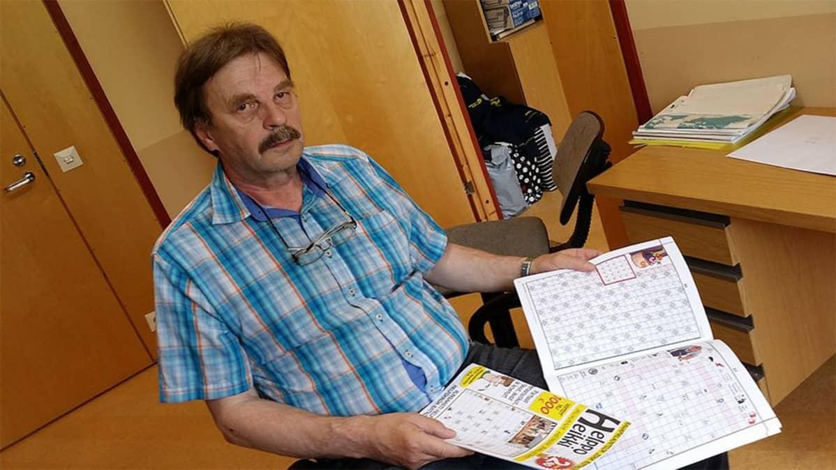 Kuvassa Sepo Hietala esittelee ristikkolehtiä.