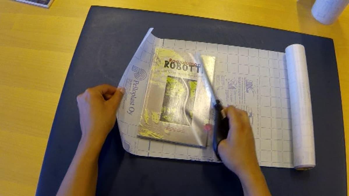 Kirjastovirkailija päällystää kirjaa oikeaoppisesti.