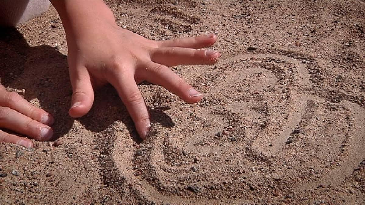 Lapsen sormi piirtää hiekkaan kuvioita.