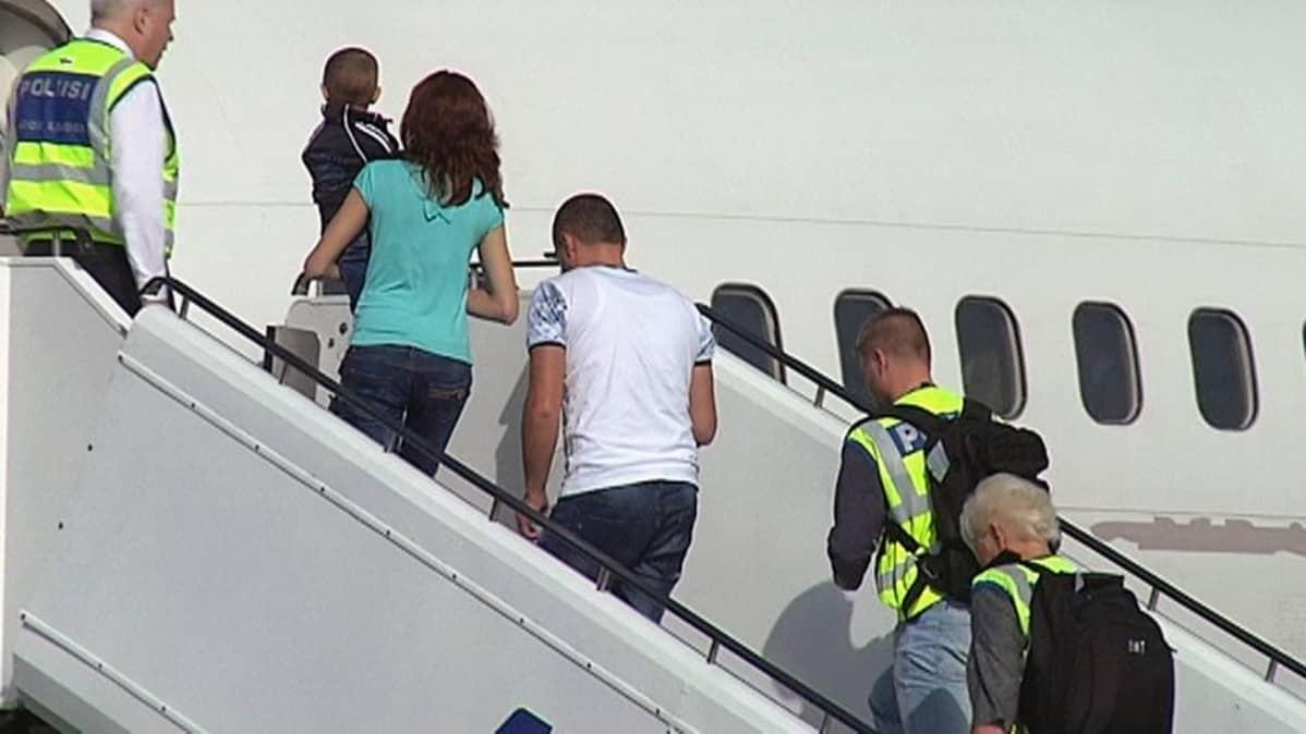 Albanialaisia kävelee poliisisaattueessa lentokoneeseen Lappeenrannassa.