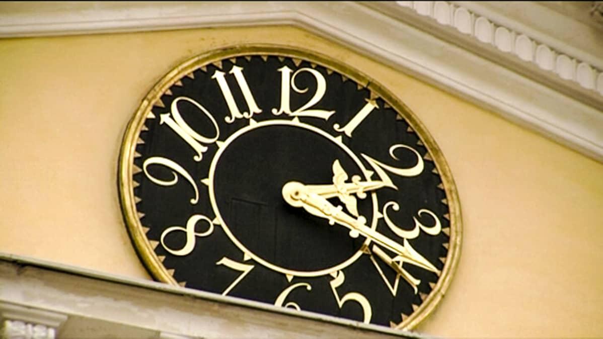 Yksityiskohta Valtioneuvoston linnan kellotaulusta. Kello on vartin yli kaksi.