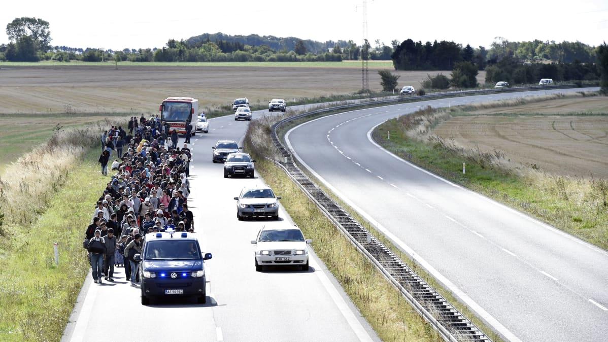 Turvapaikanhakijat kävelevät Tanskan ja Ruotsin välisellä moottoritiellä.