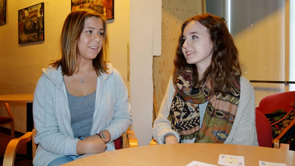 Kaksi tyttöä istuu nuorisotalon pöydän ääressä.