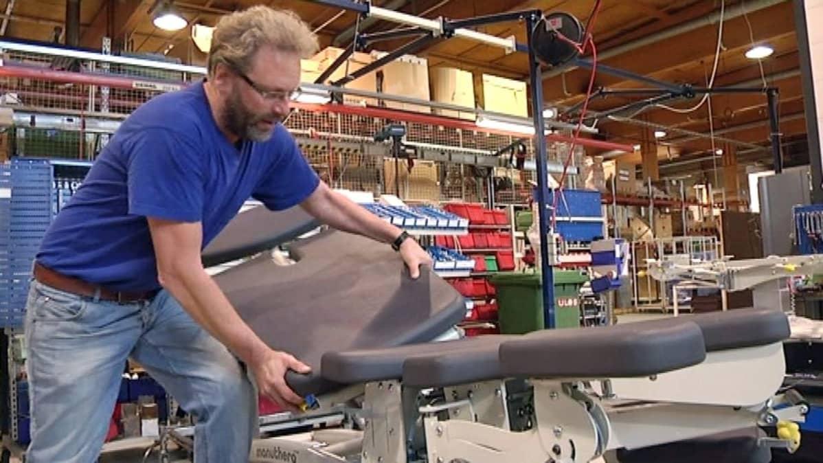 Lojerin tehtaan työntekijä näyttää hoitopöydän toimintoja