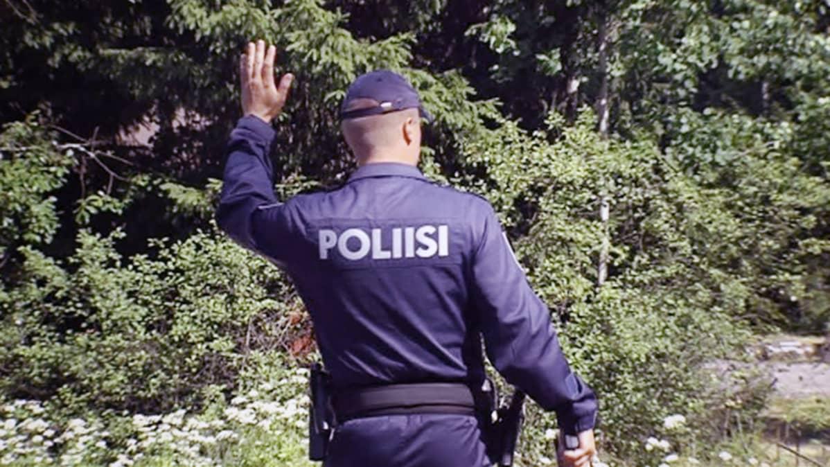 Poliisi pysäyttää liikennettä maantiellä.