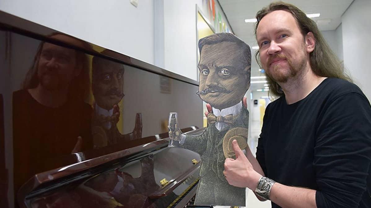 Juha-Pekka Koskinen pianon ääressä pahvi-Sibeliuksen kanssa