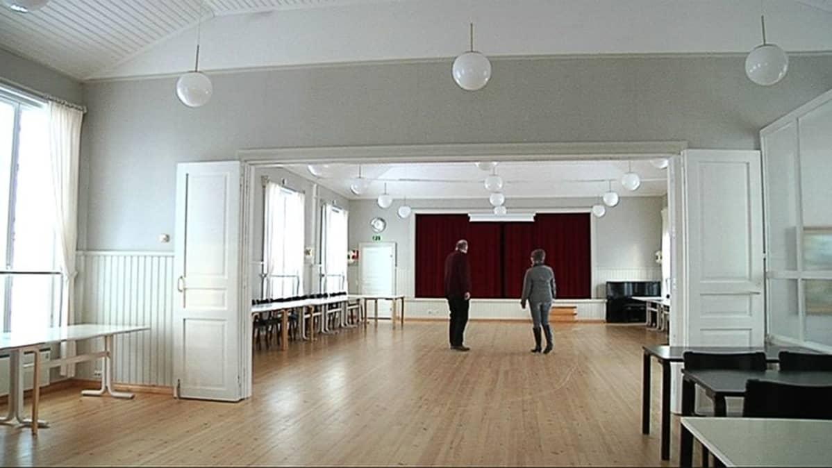 Kuvassa työväentalon sali, jossa kaksi henkilöö katselee.