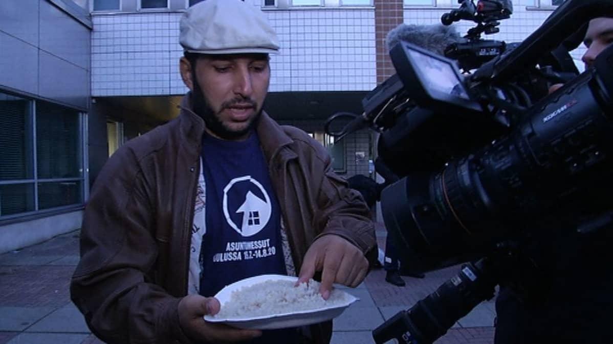Turvapaikanhakija esittelee ruoka-annostaan Oulun poliisitalon edessä keskiviikkona.