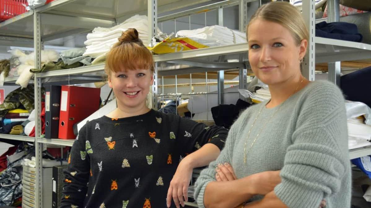 Luova johtaja Tiia Vanhatapio ja suunnittelija Lilli Norio vaateyrityksen leikkaamossa.