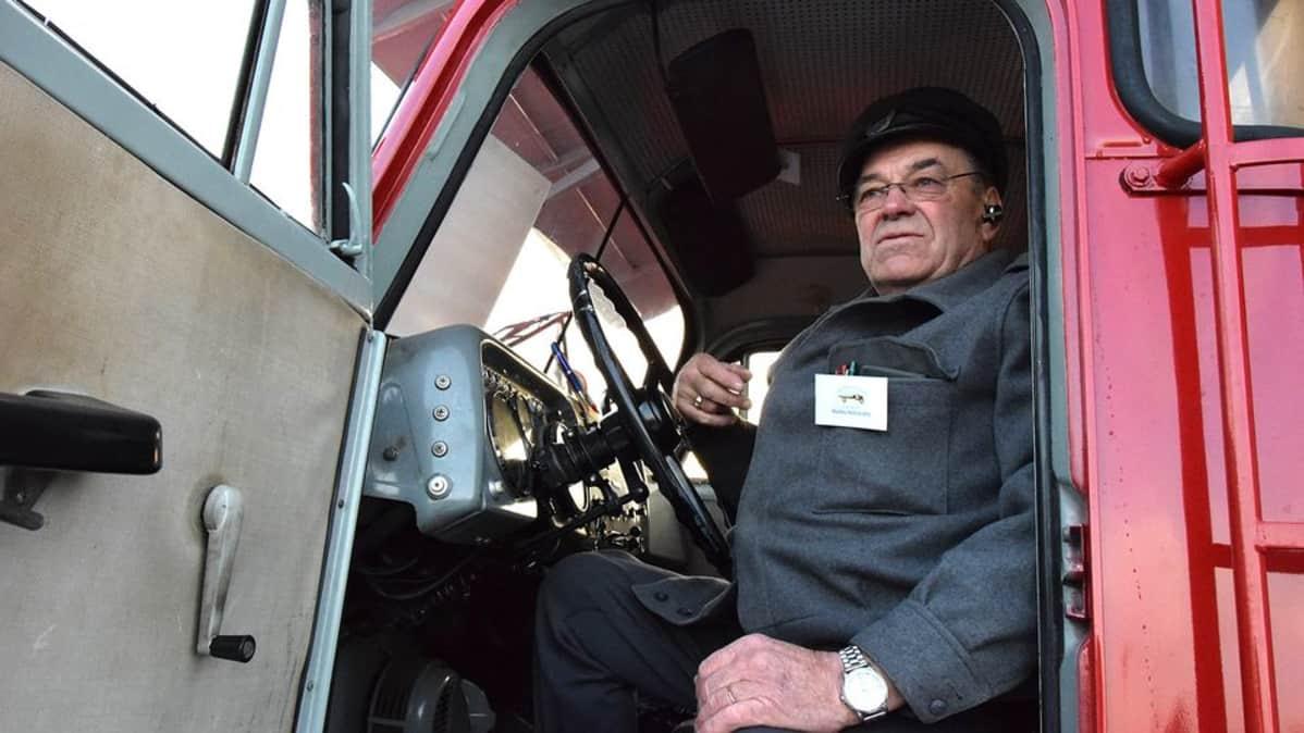Mies istumassa vanhan kuorma-auton ohjaamossa