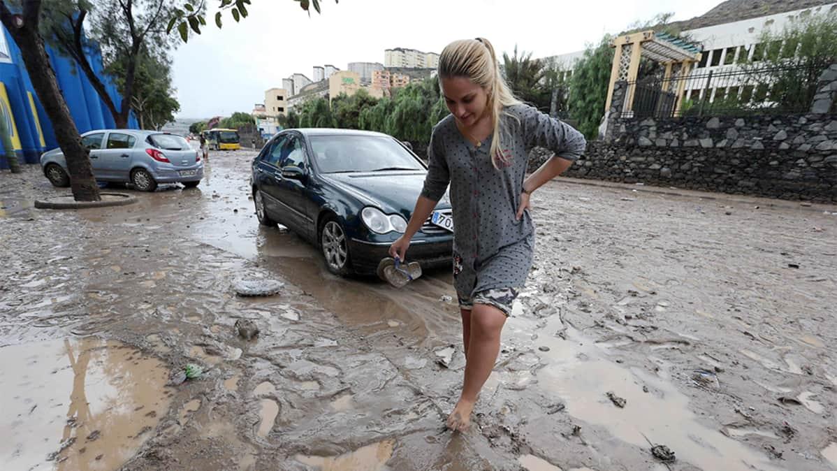 Nainen kävelee ilman kenkiä mutaisella autotiellä.