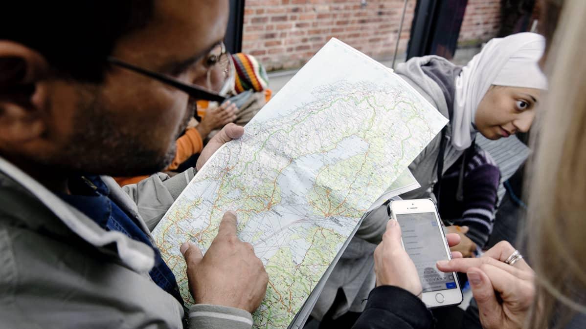 Ruotsiin saapuneet turvapaikanhakijat tutkivat karttaa Malmön rautatieasemalla.