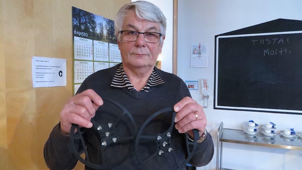 Keminmaan vanhusneuvoston puheenjohtaja Lasse Vaaraniemi kädessään kenkien liukuesteitä.