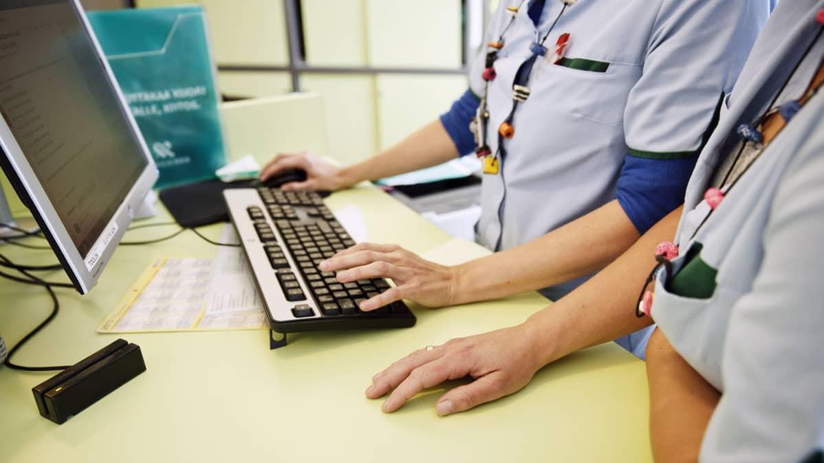 Sairaanhoitajat käyttävät tietokonetta yksityisellä lääkäriasemalla Helsingissä.