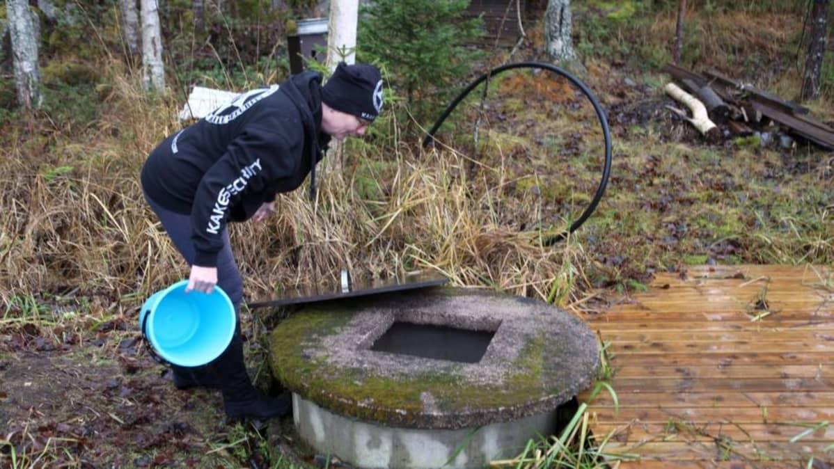 Leena Luostarinen tarkistaa päivittäin, että lähteessä on vettä Jussin kannettavaksi.