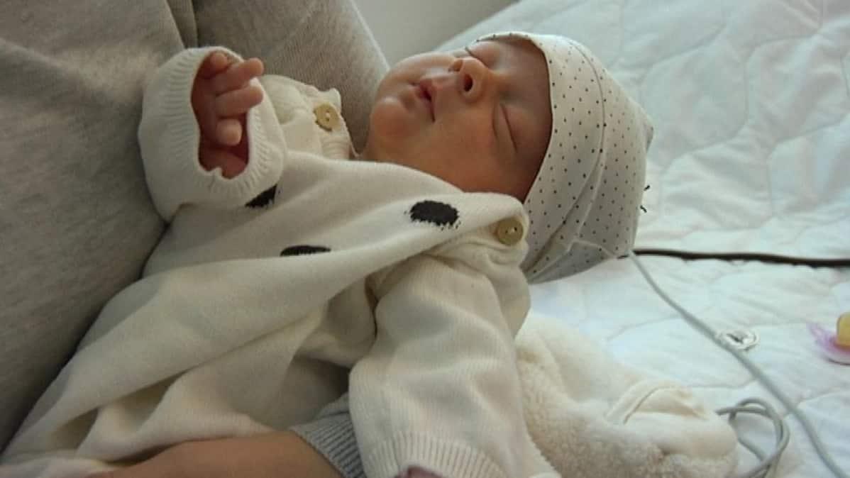 Keskosena syntynyt Emma nukkuu äitinsä käsivarsilla Tyksin keskolassa.