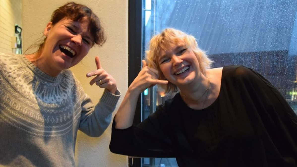 Naurujoogaohjaaja Sirpa Soininen ohjaa toimittaja Kati Turtolaa naurujoogaharjoituksessa.