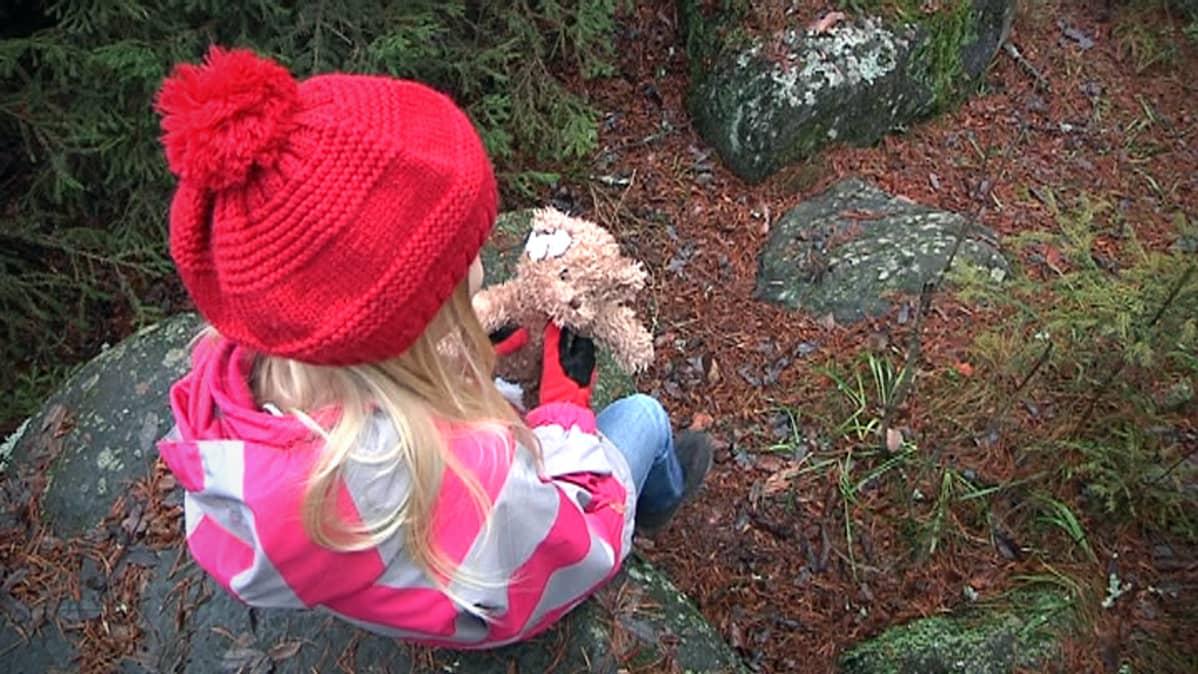 Lapsi istuu kivellä nalle sylissä.