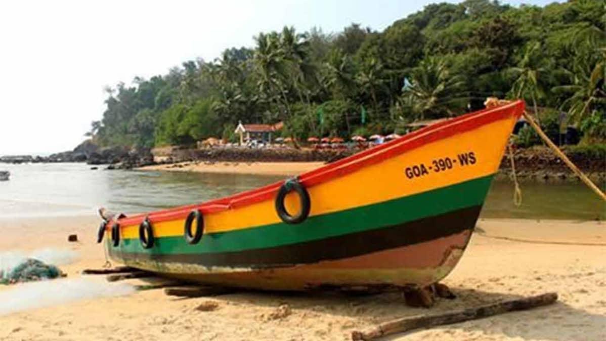 Värikäs vene hiekkarannalla, taustalla metsää, terassi, jossa päivänvarjoja.