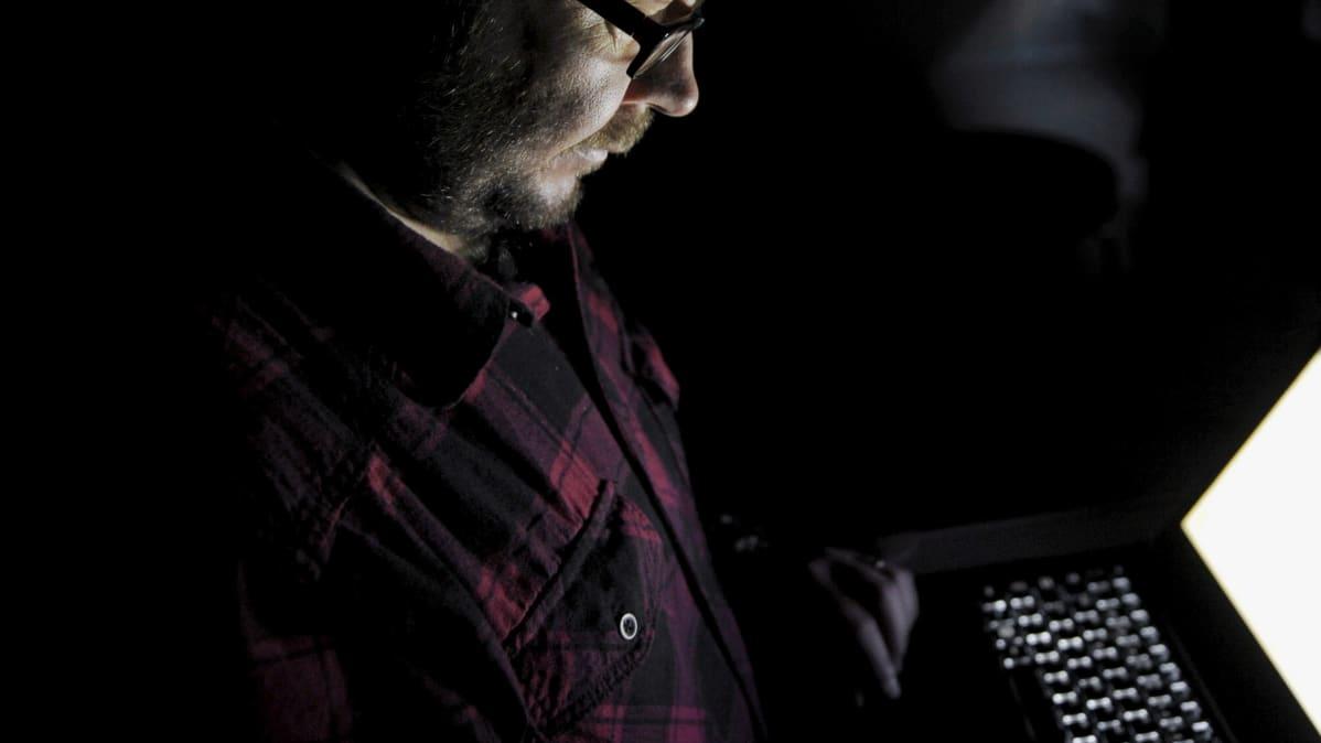 Mies ja kannettava tietokone.
