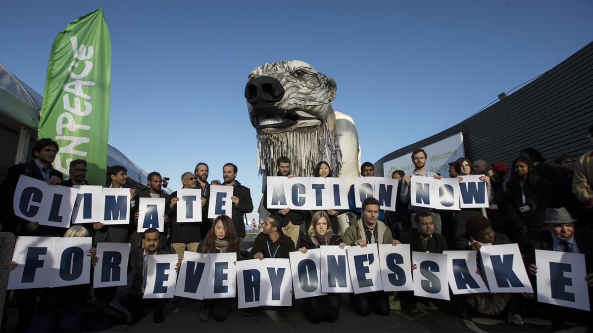 """Reilu parikymmentä ihmistä pitelee käsissään kirjaimia joista muodostuu lause """"climate action now for everyone's sake""""."""