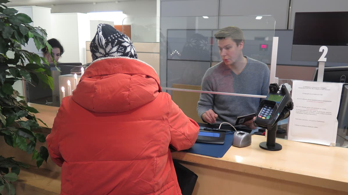 Asiakas hakemassa passia lupapalveluiden tiskiltä.